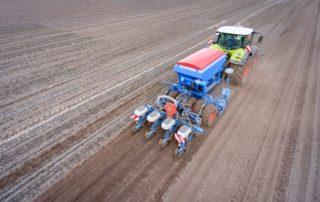 Traktor mit moderner Maislegetechnik auf dem Feld, Luftbild