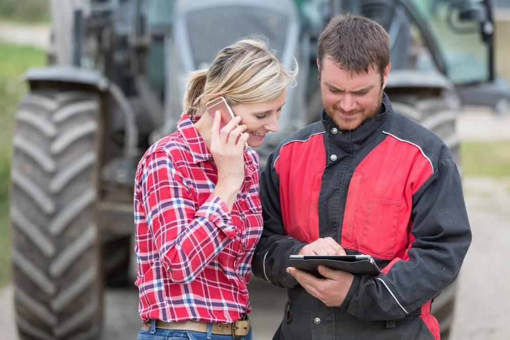 Mann und Frau schauen gemeinsam auf ein Tablet-PC, Frau telefoniert dabei. Im Hintergrund steht ein Trecker.