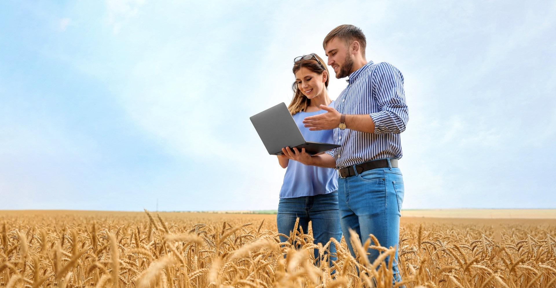 Junge Agronomen auf einem Feld mit einem Laptop