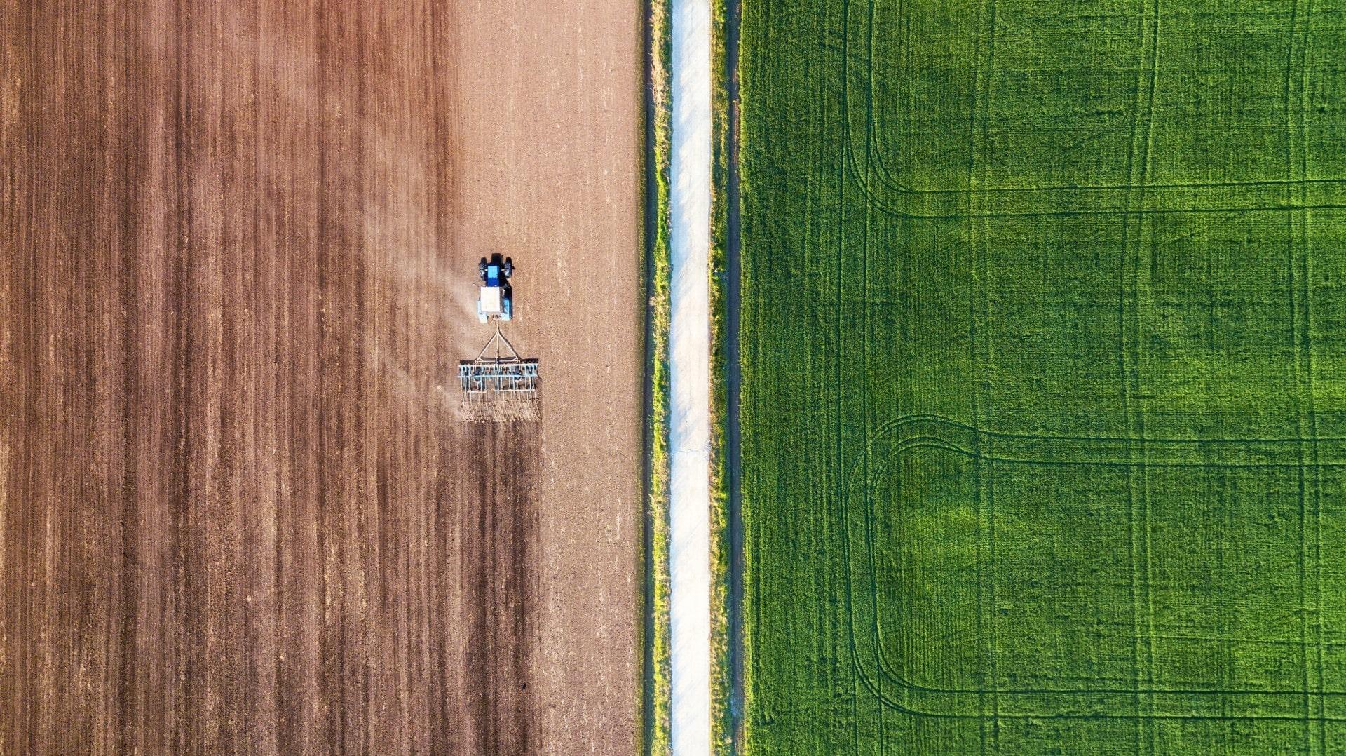 Luftbild von einem Feld, Mähdrescher auf dem Feld.